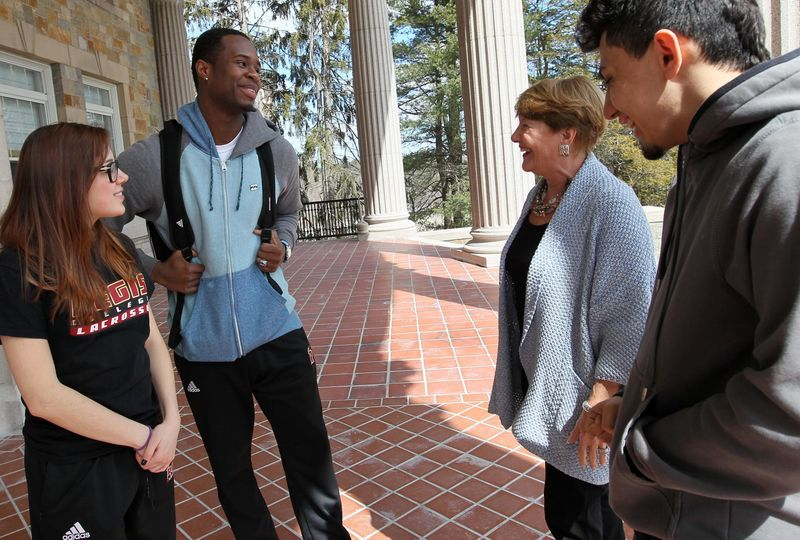Regis College president Antoinette Hays (second from right) talked with students last month. From left: Julia Jones, Sam Jean-Gilles, and Chris Cortez, of Framingham.